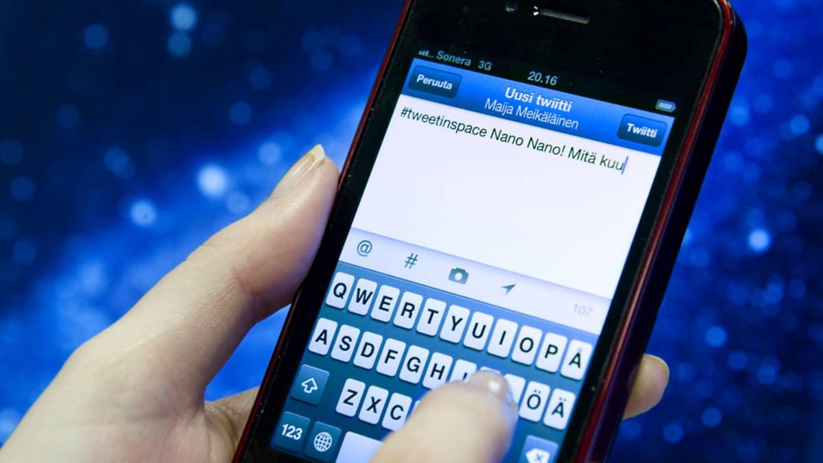 Henkilö kirjoittaa twiittiä älypuhelimella, taustalla kuva avaruudesta.