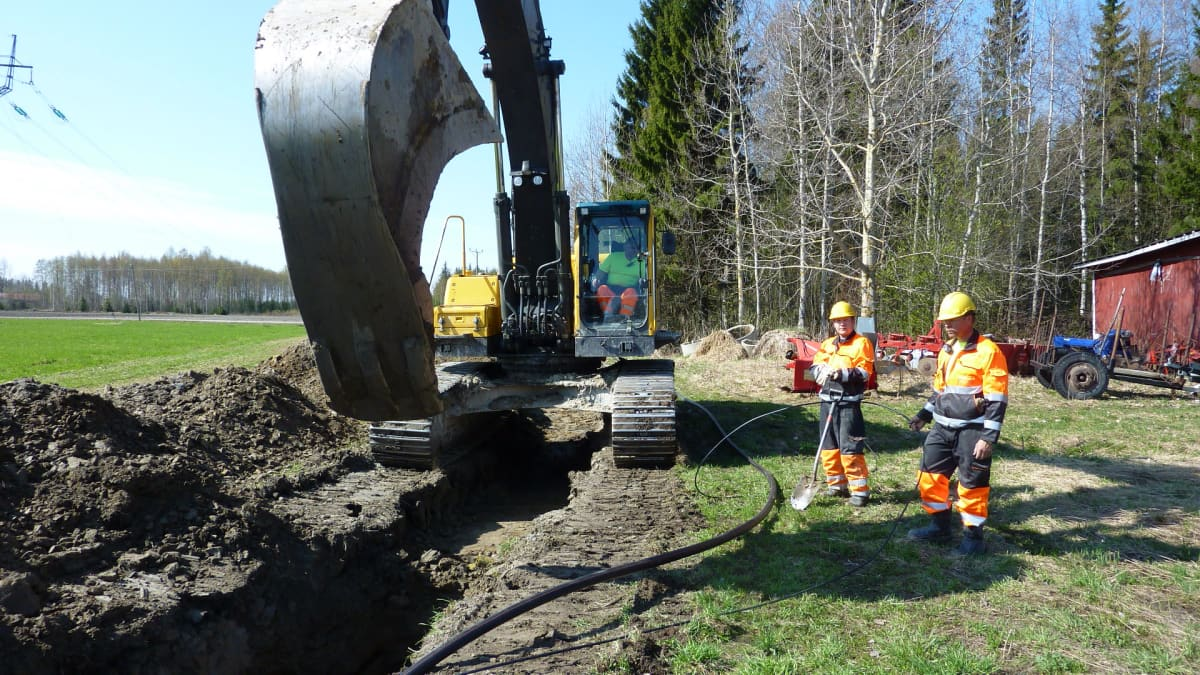 Kaivinkone kauhoo kaivantoa viemäriputkelle ja valokuitukaapelille