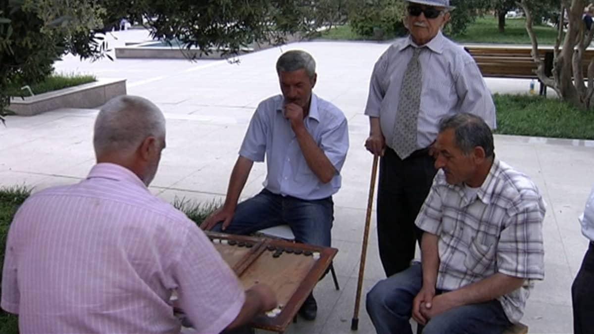 Azerbaidzhanilaismiehet pelaavat kadulla lautapeliä.