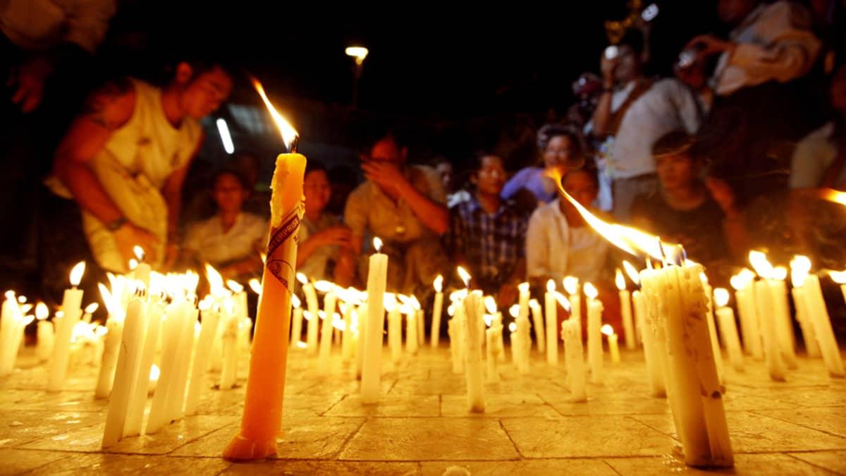 Mielenosoittajat sytyttivät kynttilöitä vastalauseena sähkövajeeseen Yangonissa, Myanmarissa, 22. toukokuuta 2012.