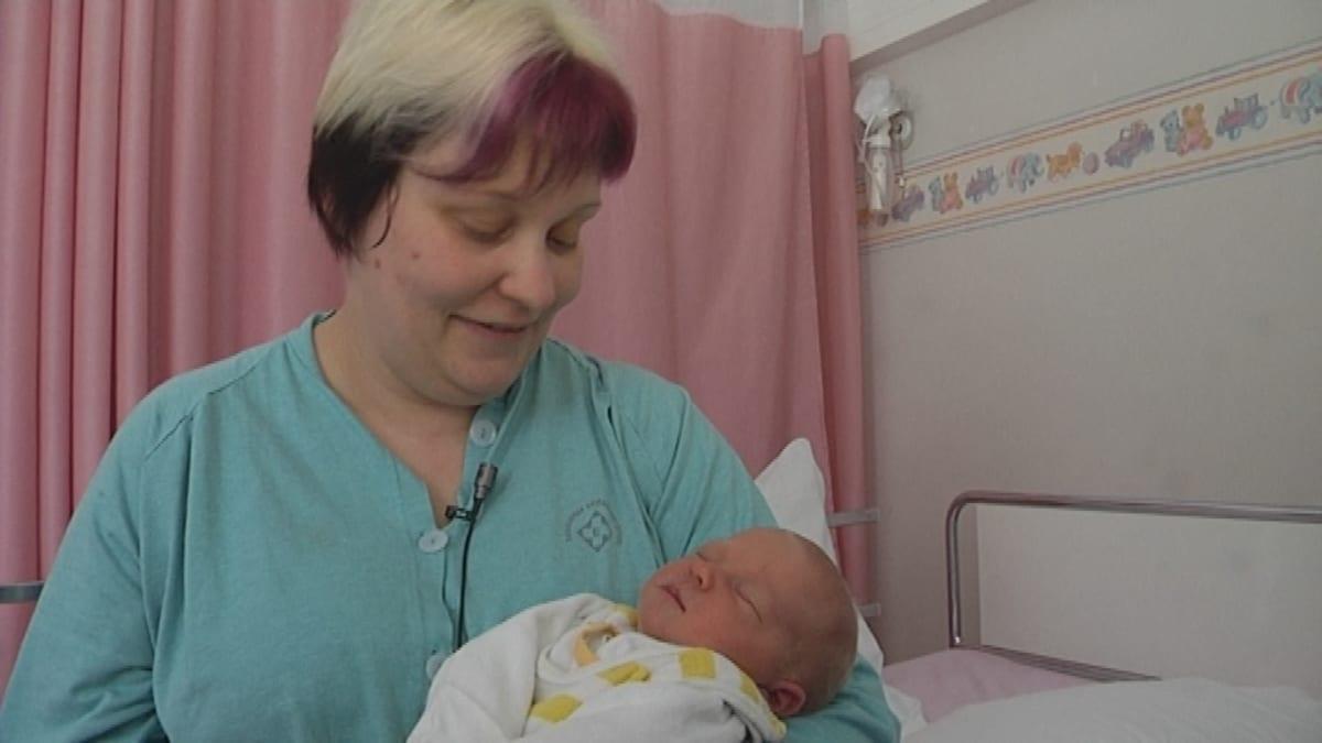 Nainen vauva sylissä synnytyssairaalan osastolla.