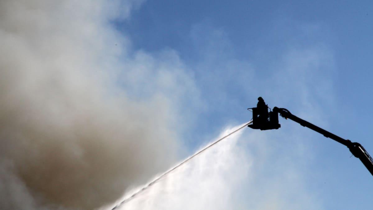 Palomies sammuttamassa Tuusulan teollisuushallin tulipaloa.