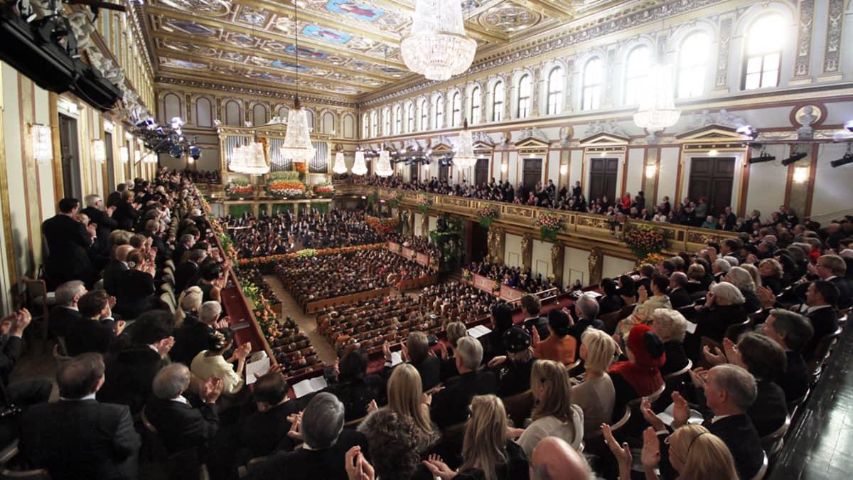 Kullalla, kukilla ja maalauksin koristettu konserttisali. Kristallikruunuja ja paljon yleisöä.