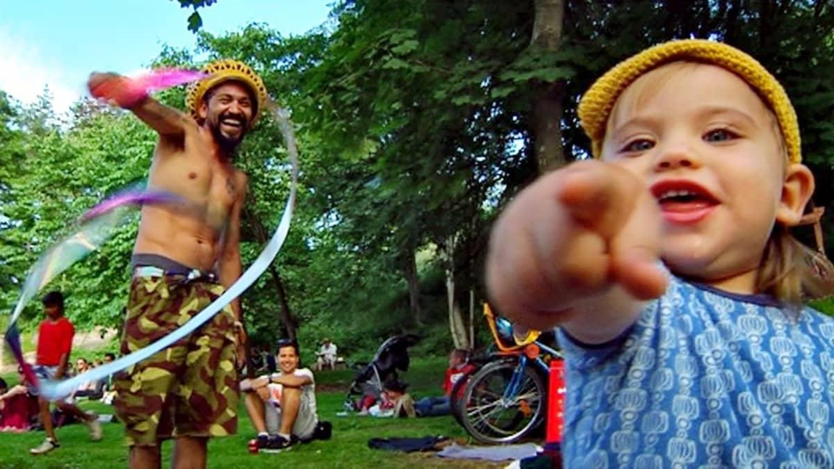 Pieni tyttö osoittaa sormellaan kameraan, takana rastapäinen tyyppi heiluttaa viuhkaa.