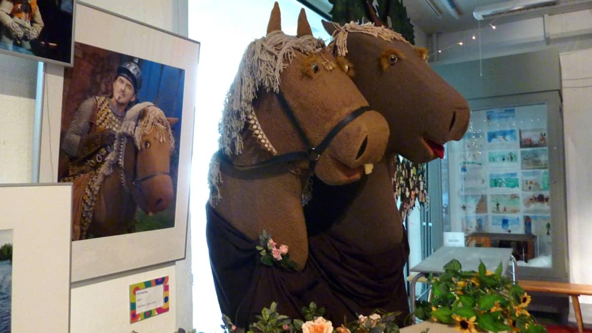 Kaksi keppihevosta sekä valokuva hevosesta ja ritarista Lastenkulttuurikeskus Rullan näyttelyssä.