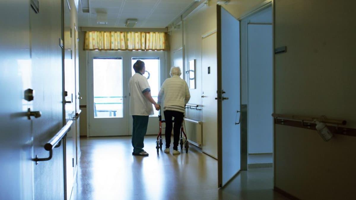 Hoitaja taluttaa vanhusta käytävällä.