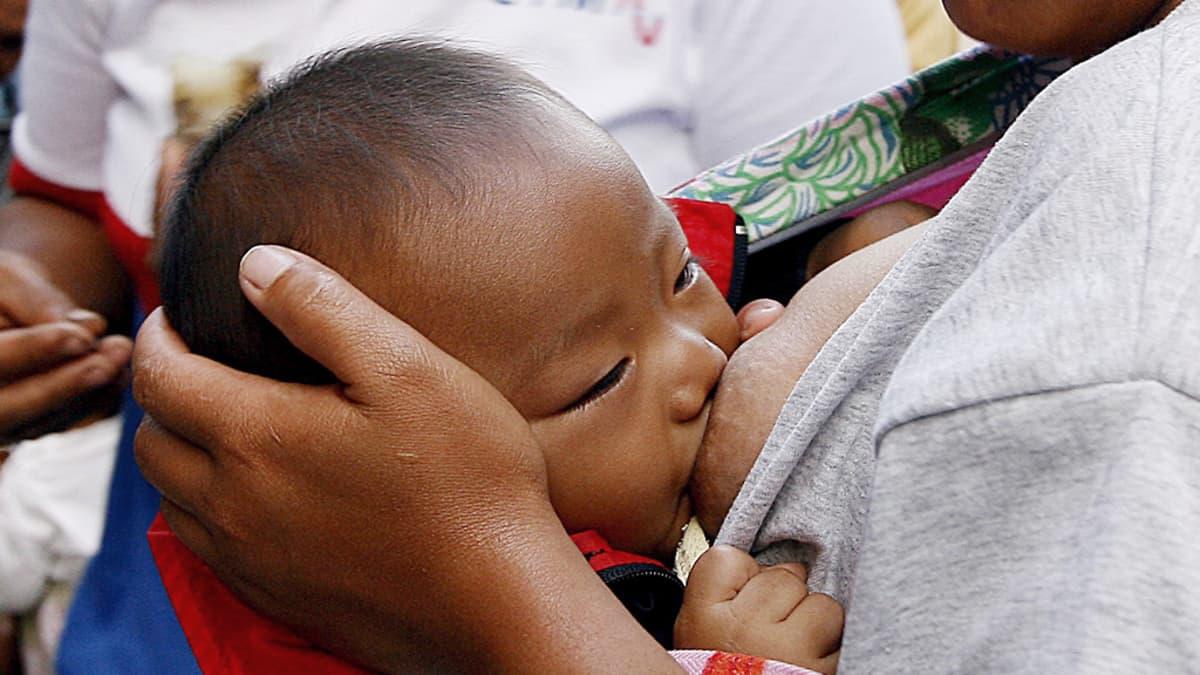 Filippiiniläislapsi imee äitinsä rintaa.
