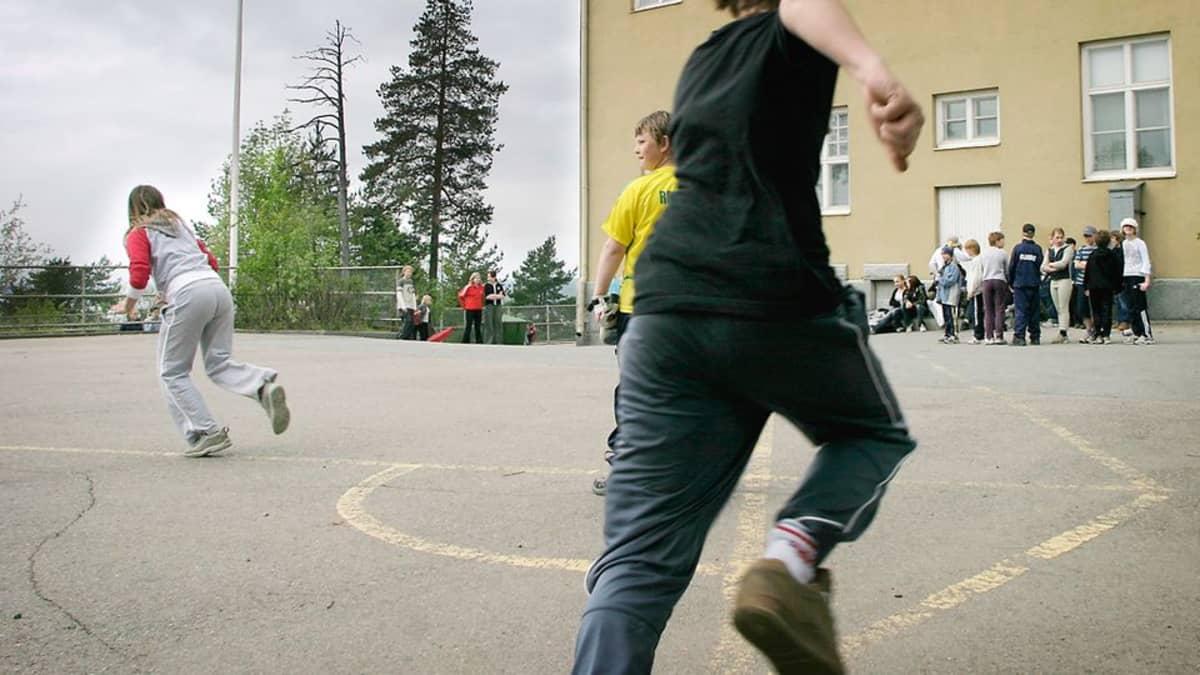 Pispan koulun oppilaita pelaamassa liikuntatunnilla koulun pihalla pesäpalloa.