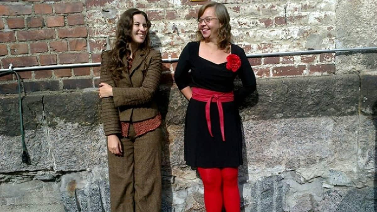 Kaksi iloista naista seisoo pihalla.