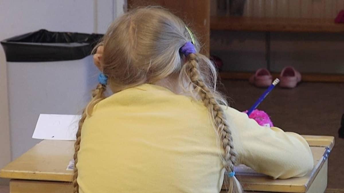 Lettipäinen tyttö istuu pulpetissa.