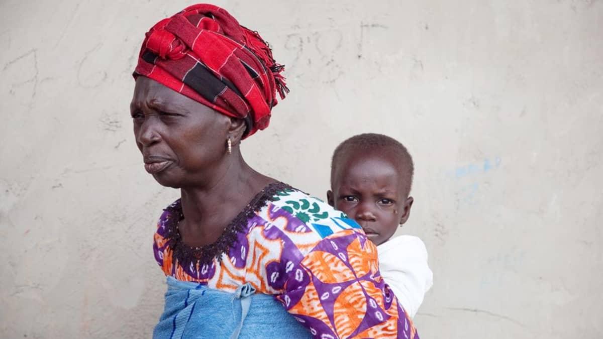Sira Benja odottaa siskonpoikansa kanssa ruokakuponkeja Punaisen Ristin jakelupisteessä Tambacoundan koululla Senegalissa.