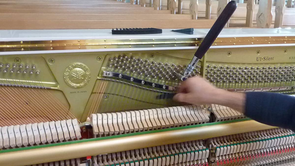Pianonvirittäjällä on apunaan viritysavain ja musta läpyskä, jolla kielet pystyy erottamaan toisistaan ja virittämään yksi kerrallaan.
