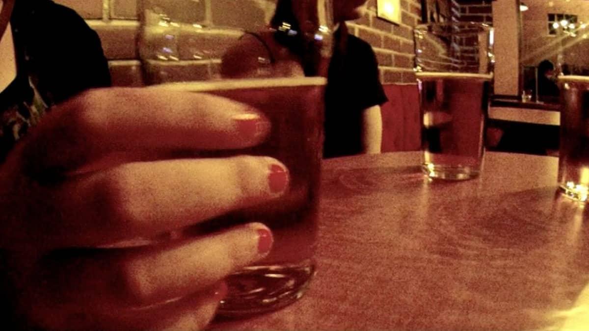 Ihmisiä pöydän ympärillä baarissa.