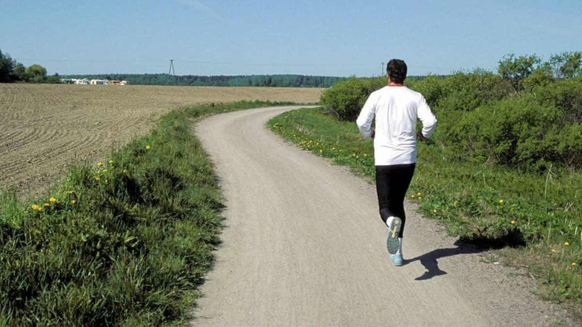Mies juoksee hiekkatiellä maalaismaisemassa.