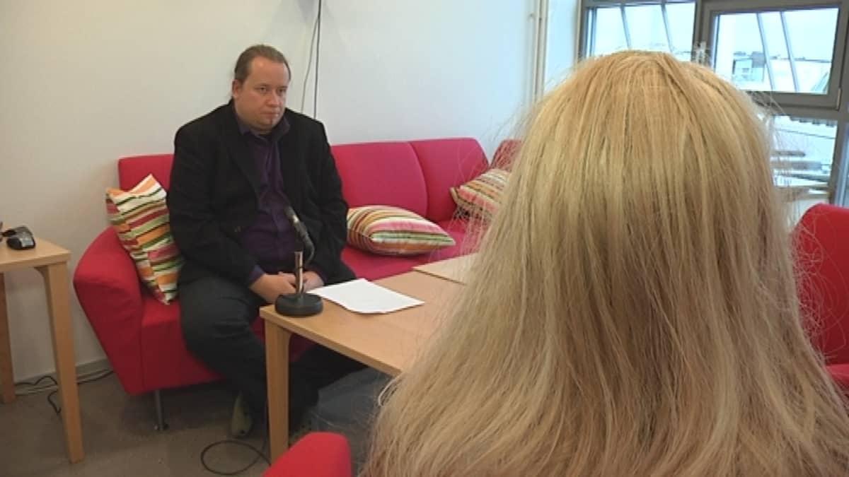 Toimittaja Jari Pelkonen haastattelee hoitajaa.