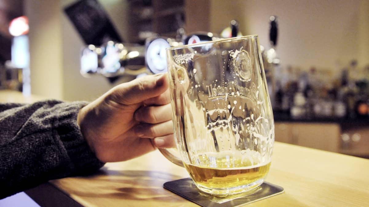 Mies juo olutta baaritiskillä.