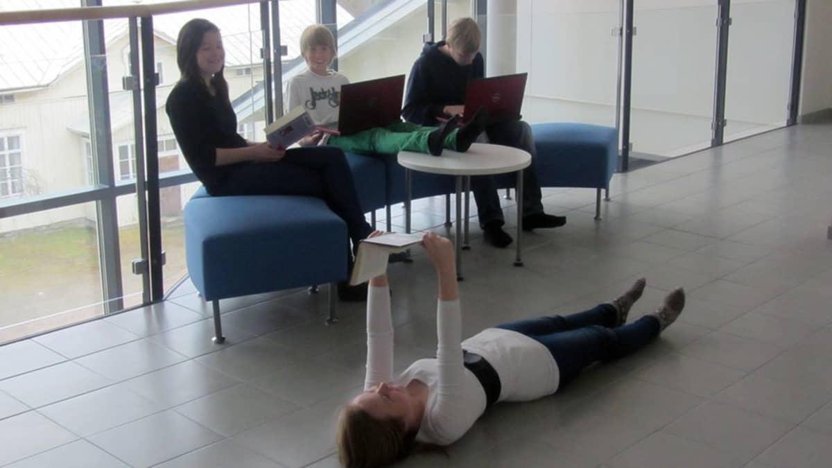 Kuvassa nuoria istuskelee sohvilla kirjojen ja läppärien kanssa, yksi nuori makaa lattialla