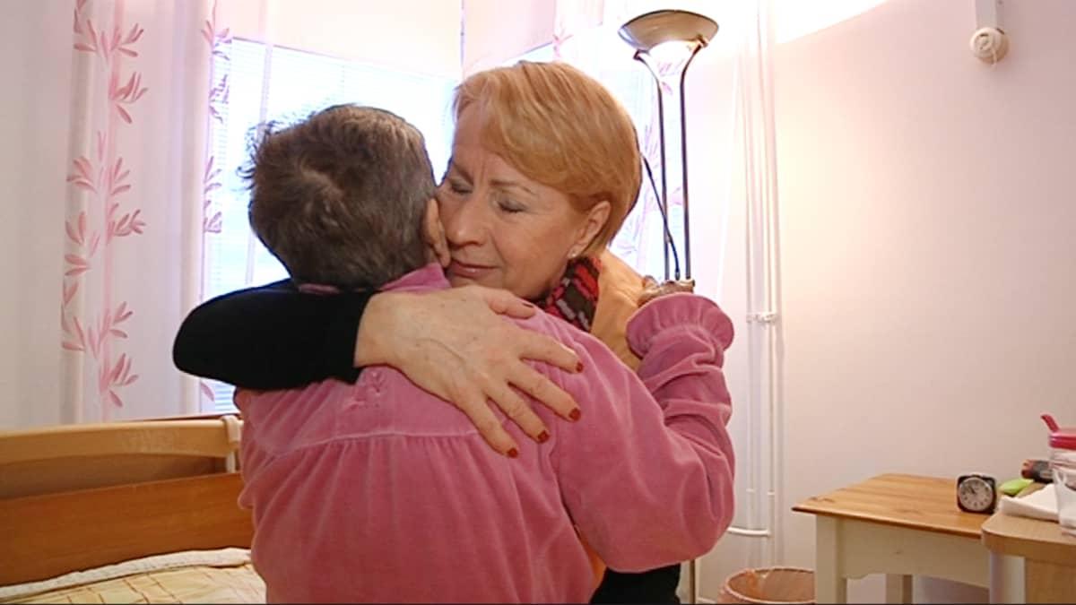 Vapaaehtoistyöntekijä Viva Lappalainen ja potilas Maija Kopakka halaavat.