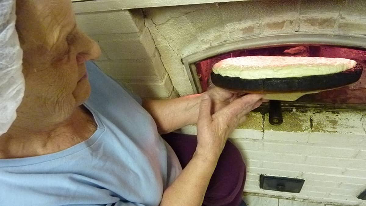 Tyyne Rautiainen laittaa juustoleivän paistumaan leivinuuniin.