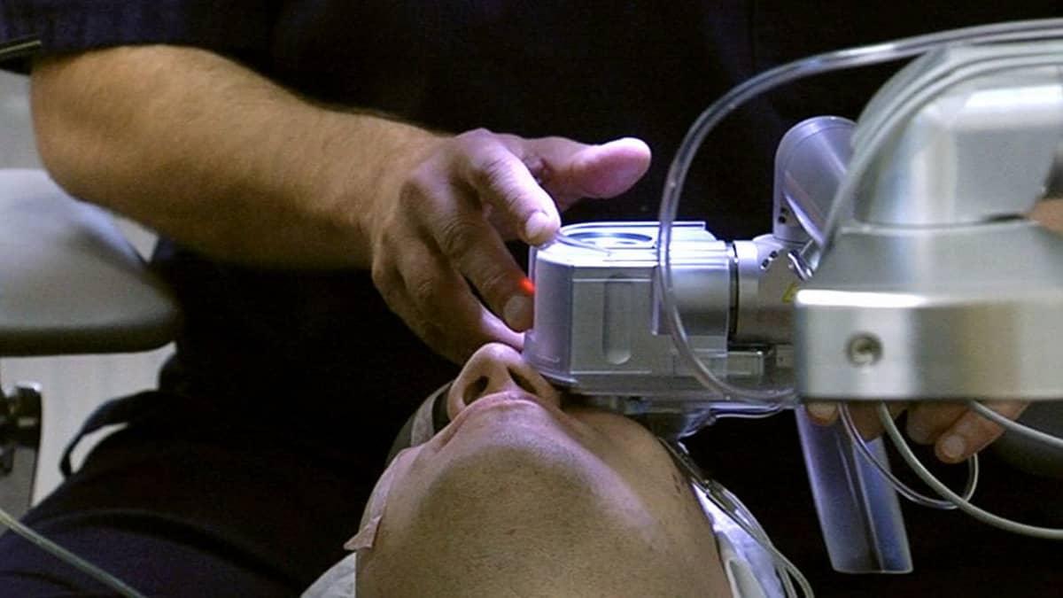 Lääkäri aloittamassa silmäleikkausta potilaalle.