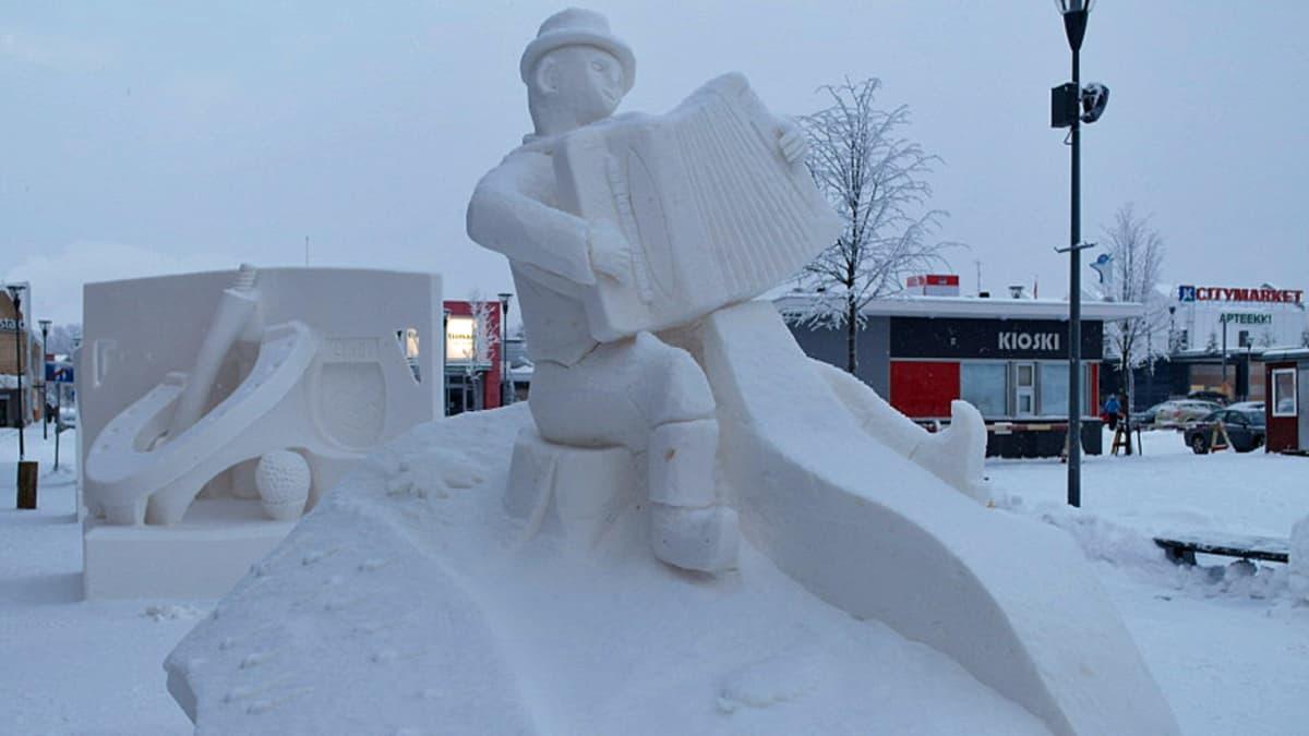 Kuva lumiveistoksesta, jossa mies soittaa hanuria