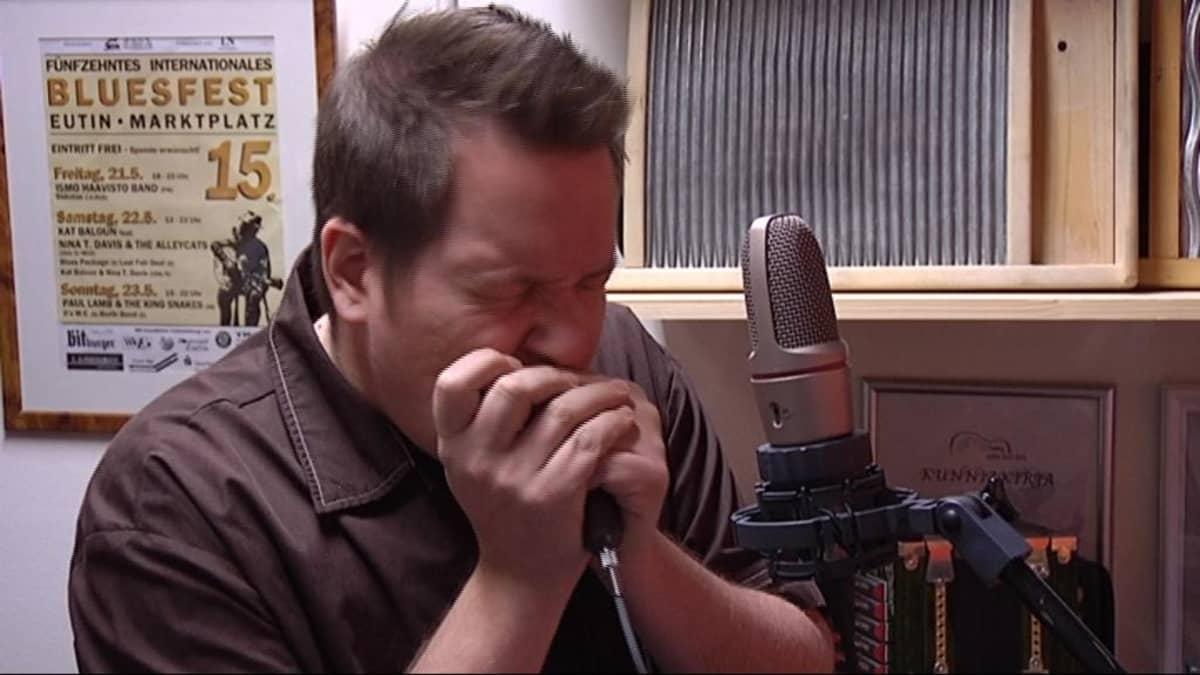 Ismo Haavisto soittaa huuliharppua tunteella.
