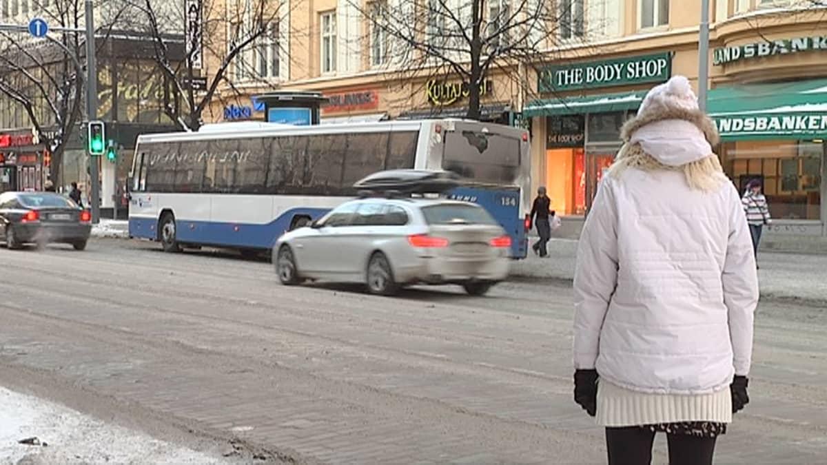 Jalankulkija katsoo autoliikennettä Hämeenkadulla.