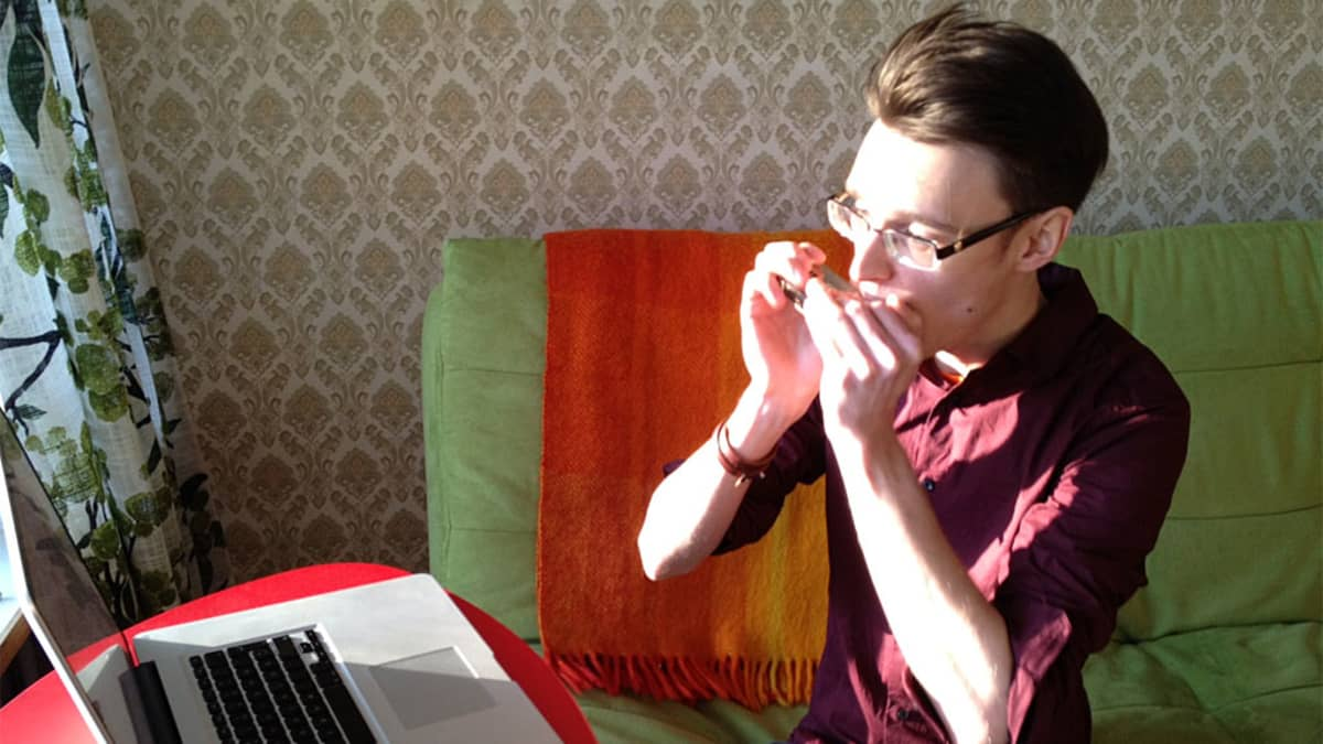 Kuvassa mies soittaa huuliharppua tietokoneen ääressä