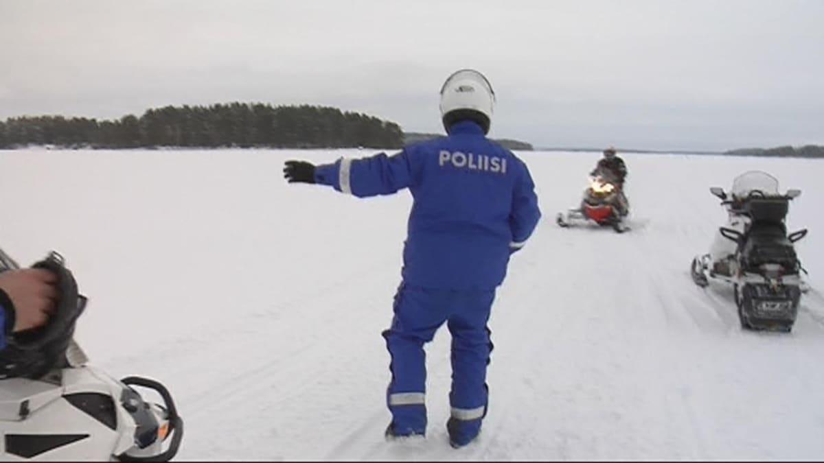 Poliisi pysäyttää moottorikelkkailijan.