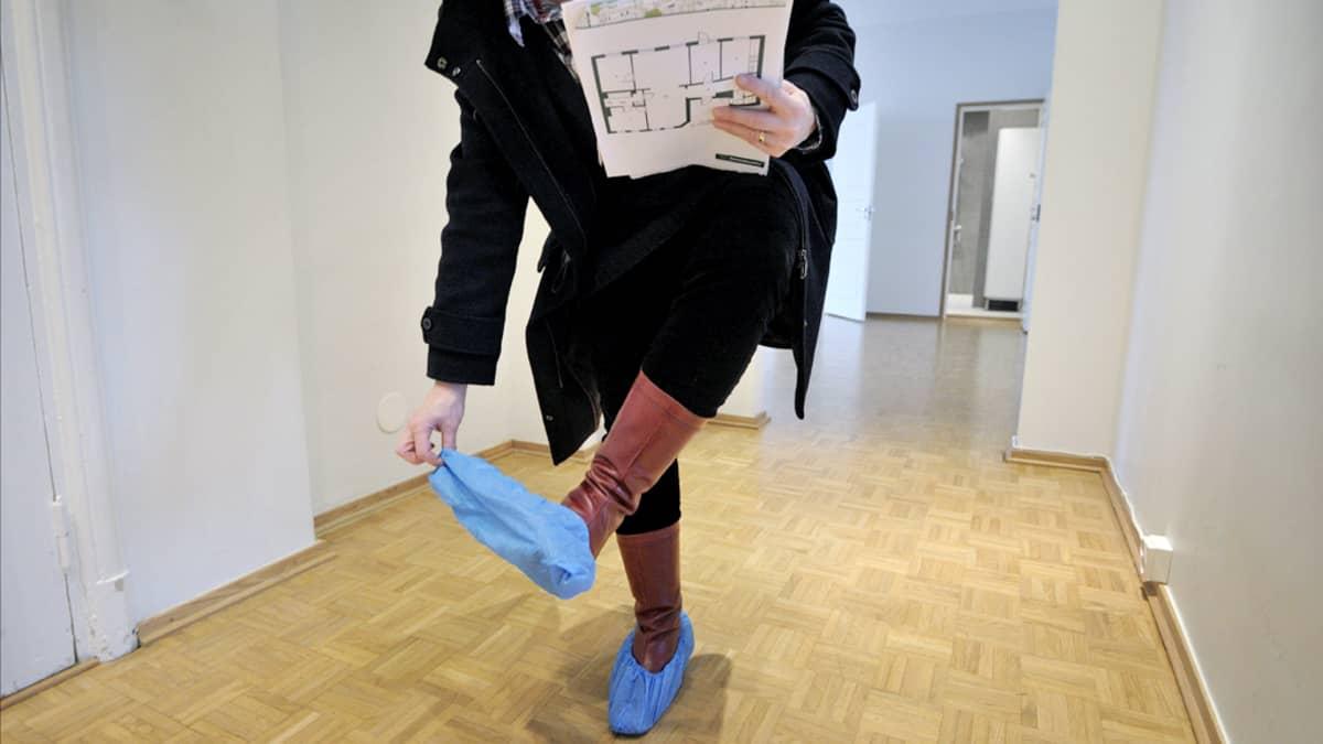 Nainen riisu suojamuoveja pois kenkänsä päältä asuntonäytössä.