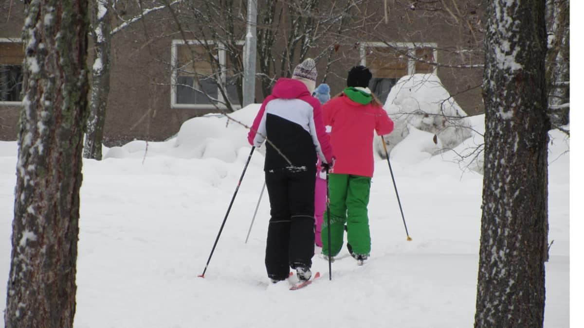Kuvassa kolme alakoululaista hiihtää värikkäissä vaatteissa pois päin kuvasta.
