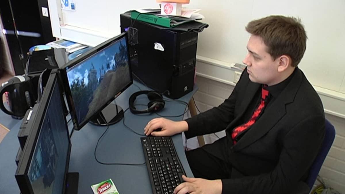 Pelisuunnittelija istuu tietokoneen ääressä