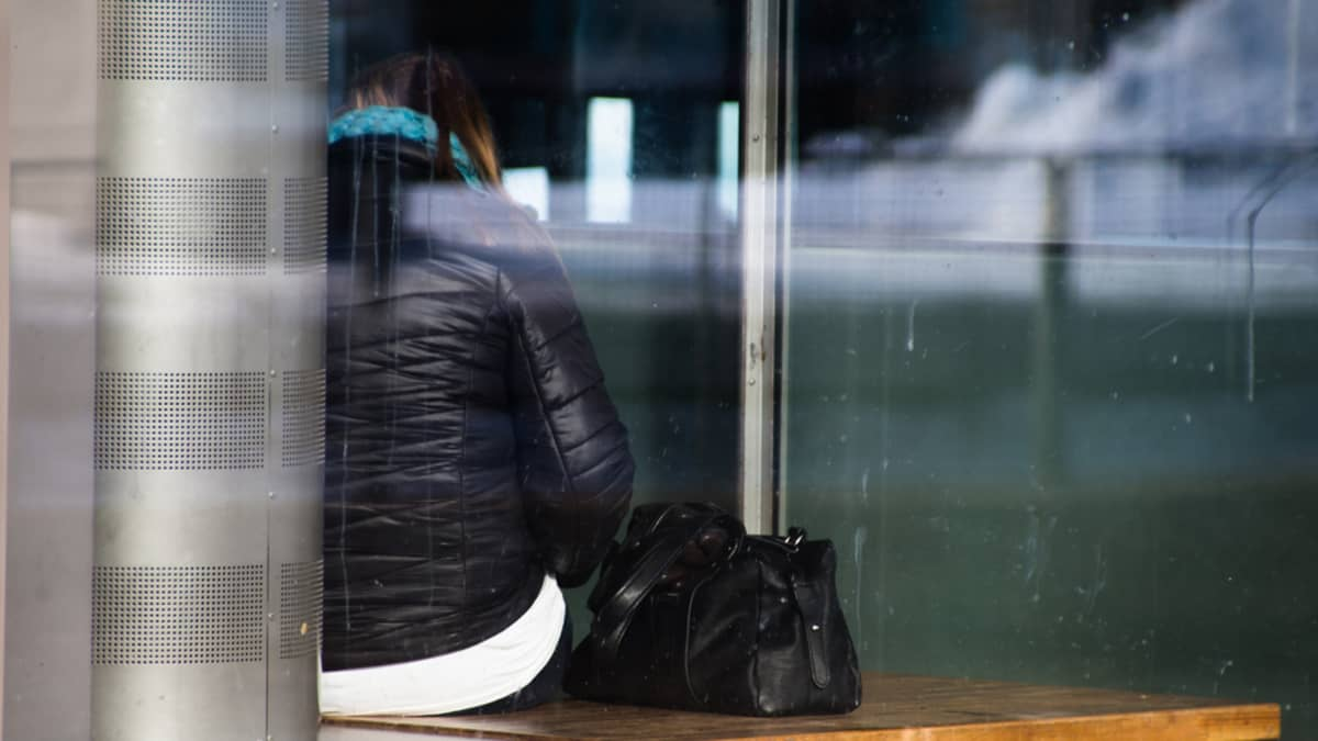 Tuntematon nainen kuvattuna selkäpuolelta istuu ikkunan takana penkillä.
