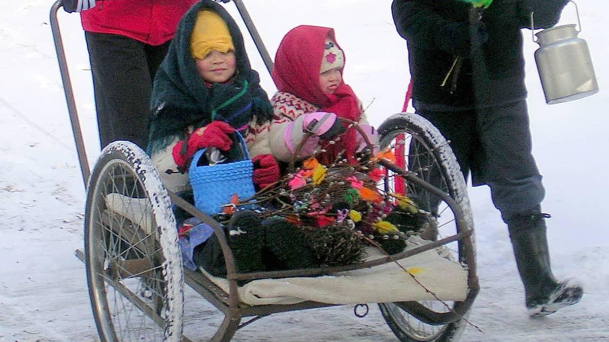 Kaksi tyttöä trulliasuissaan maitokärryissä. Vierellä hinkki kädessä kulkeva poikatrulli