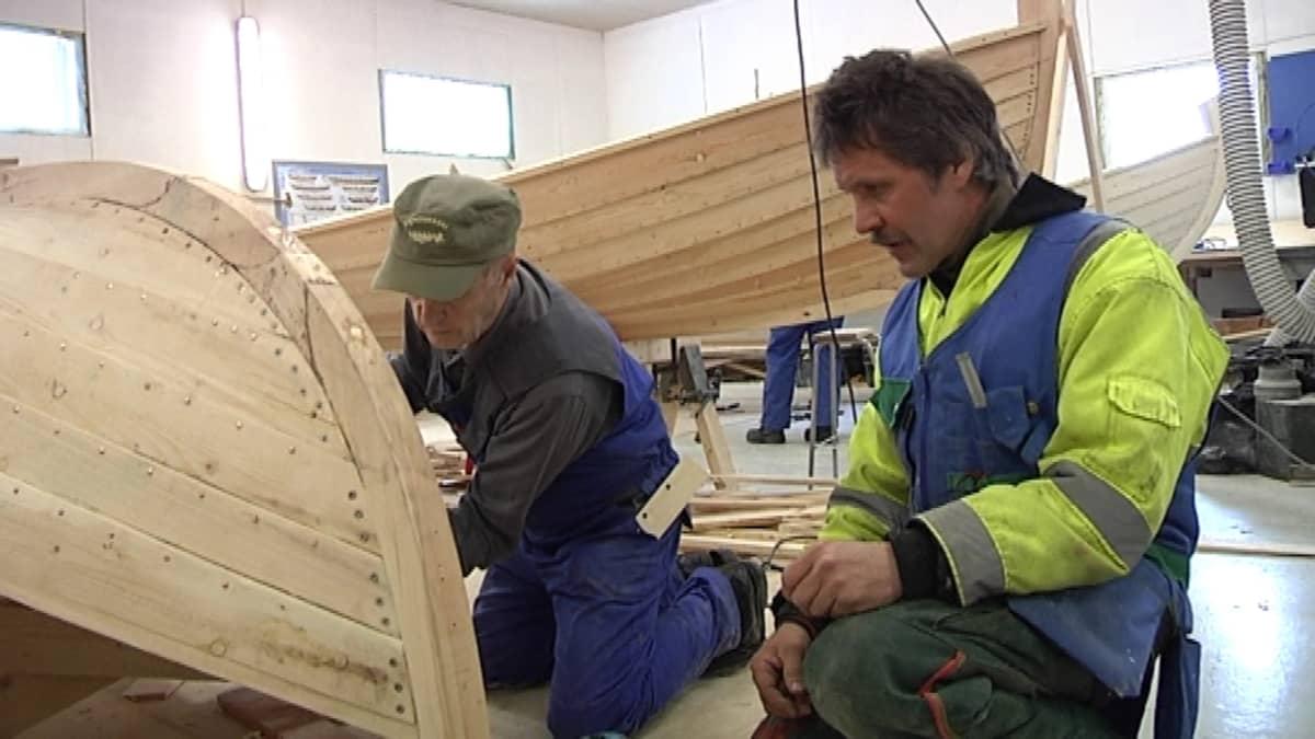 Veneen rakentamisen opettaja Jukka Lindeberg neuvoo kurssilaista puuveneen rakentamisessa.