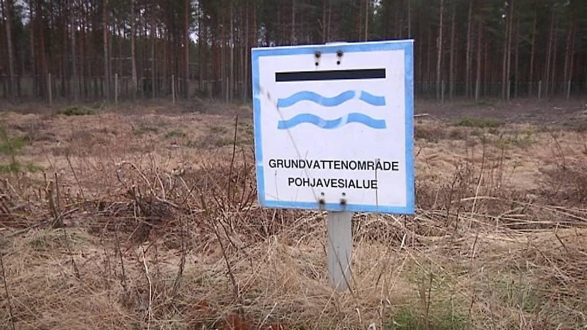 Pohjavesialueesta kertova kyltti maastossa.