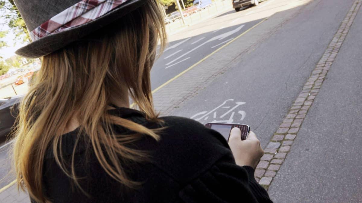 Nuori nainen surffaa kännykällään internetissä kävellessään kadulla.
