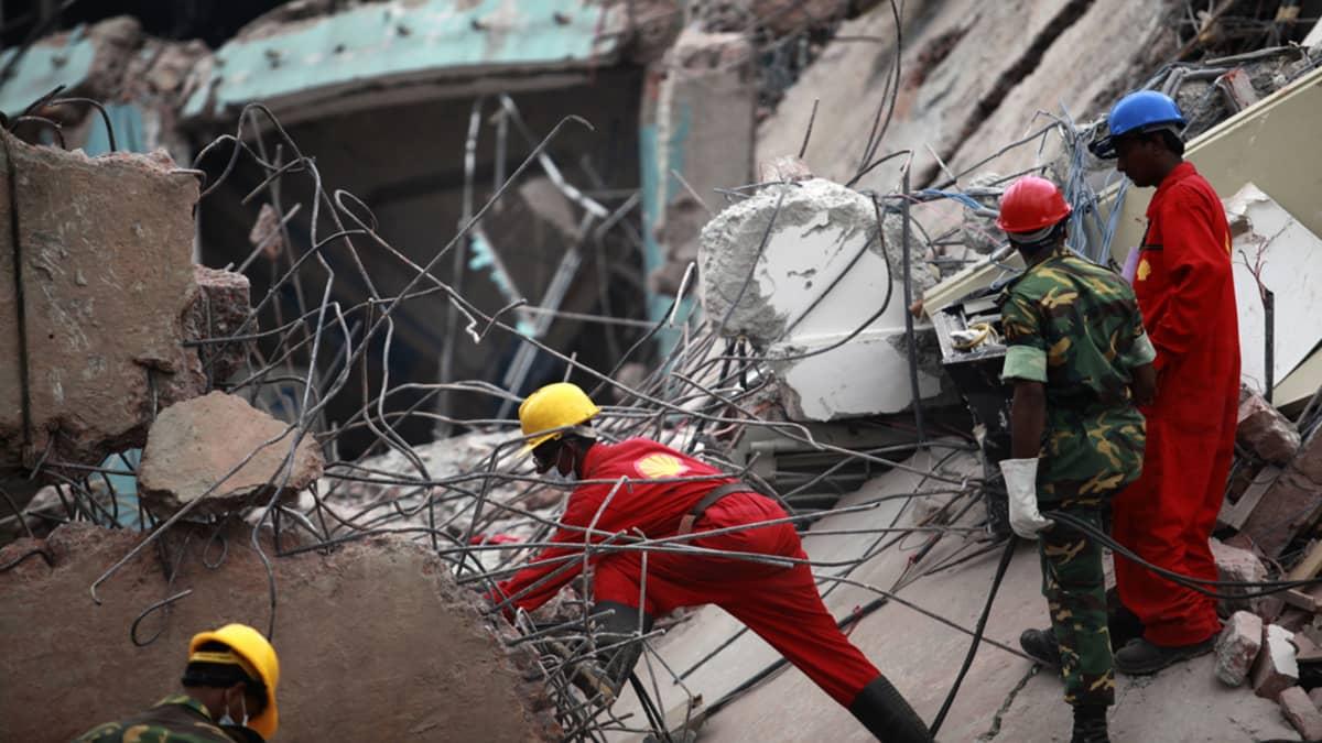 Pelastustyöntekijät etsivät eloonjääneitä romahtaneen rakennuksen raunioista Dhakassa.