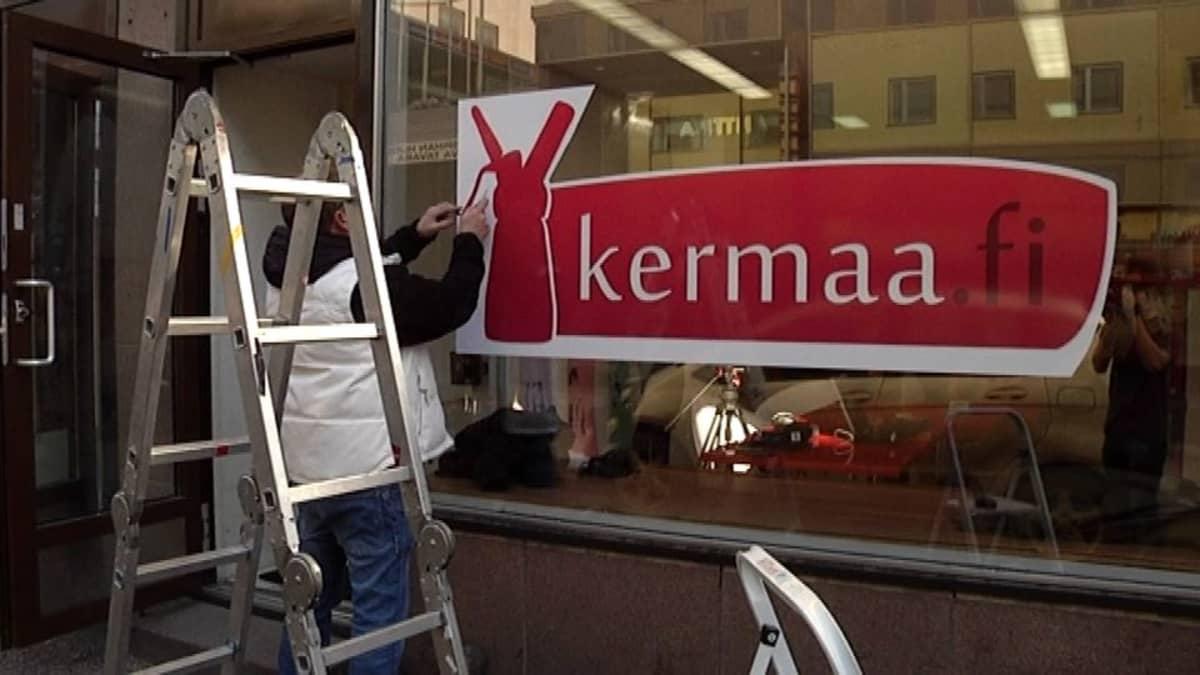 Mies teippaa liikkeen mainosta ikkunaan.