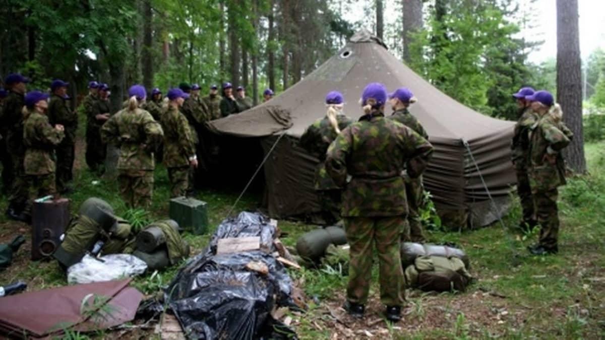Naisten Valmiusliiton leiriläisiä teltan luona metsässä.