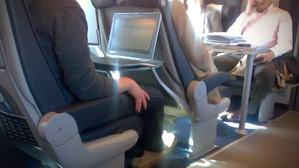 Kuvassa mies käyttää tietokonetta junassa.
