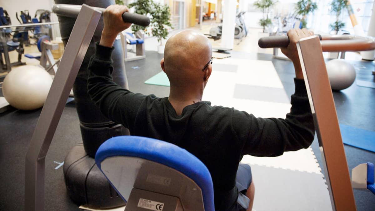 Mies treenaa kuntosalilla.