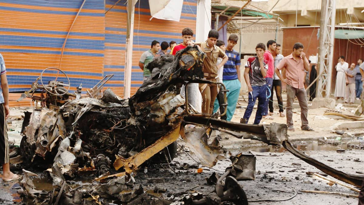 Irakilaisnuoria autopommi-iskussa tuhoutuneen auton edustalla itäisessä Bagdadissa 20. toukokuuta 2013.