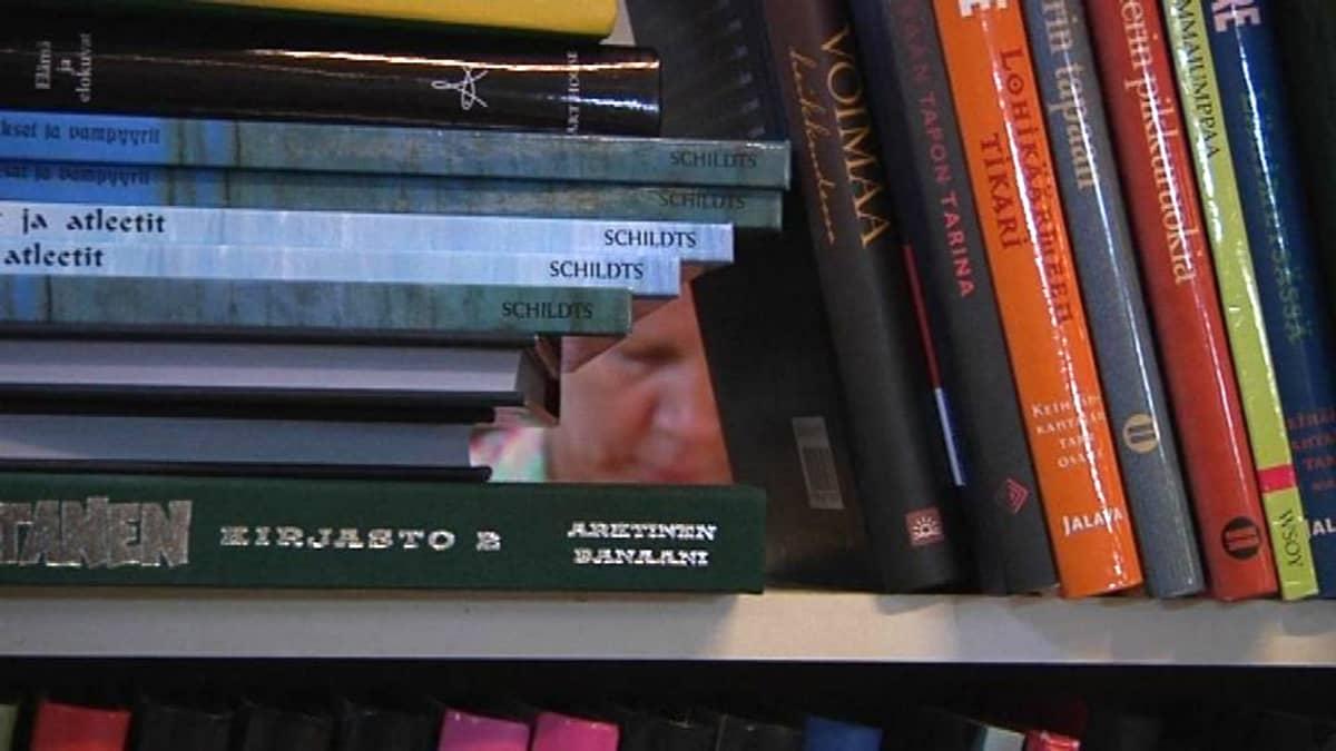 Ihmisen kasvot näkyvät kirjojen takaa.