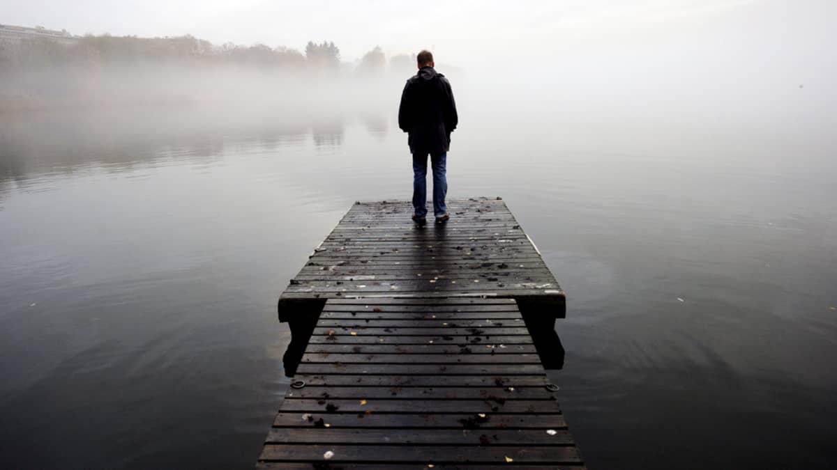 Yksinäinen mies seisoo laiturilla Helsingin Töölönlahdella.