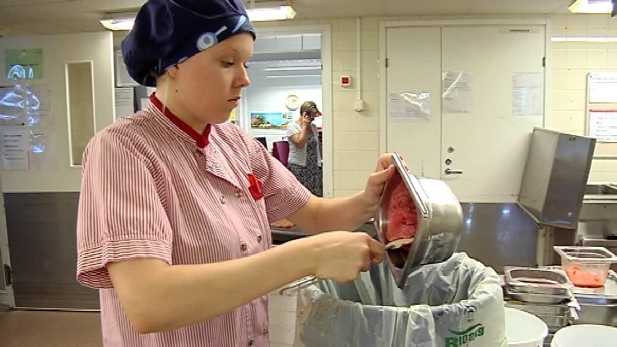 Nainen laittaa ruokaa roskiin.