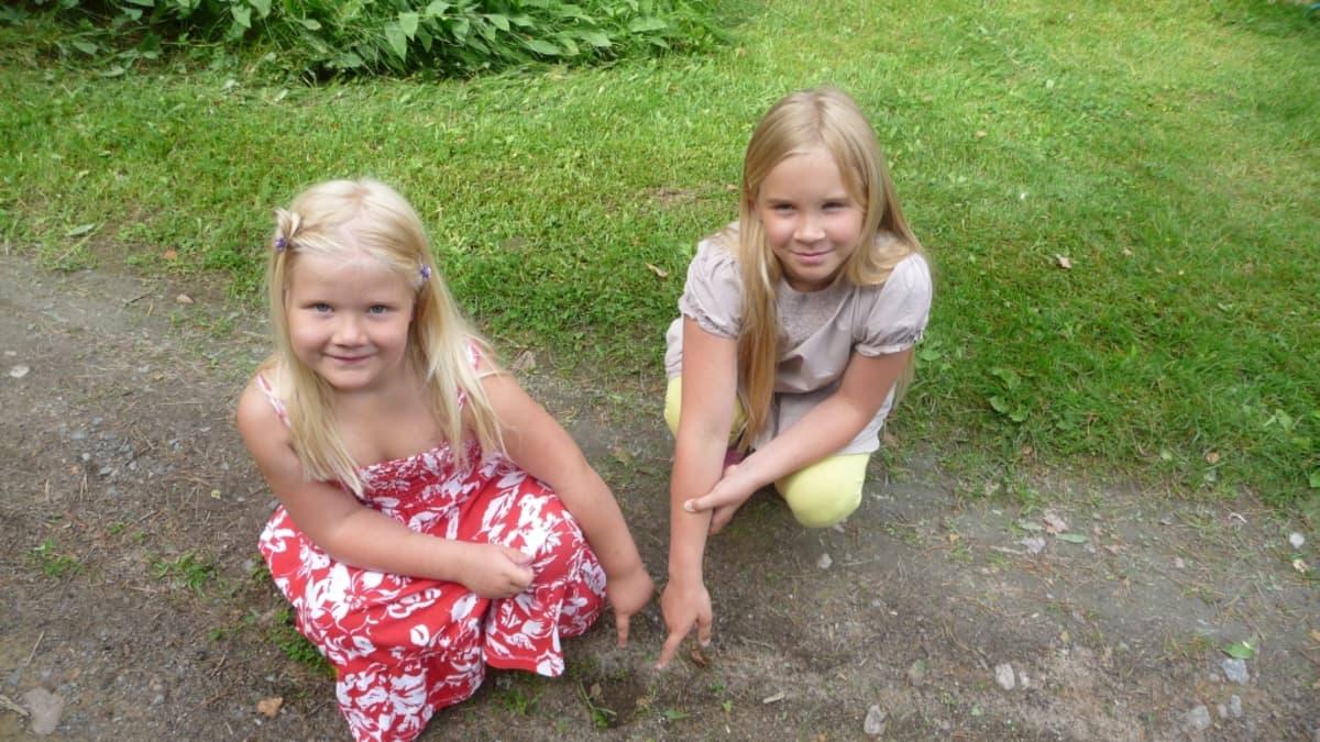 Kaksi tyttöä osoittaa sormella maahan