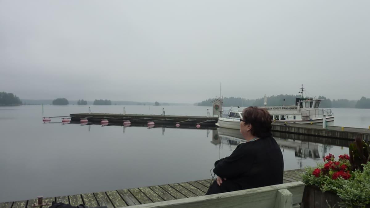Nainen istuu penkillä järven rannalla.