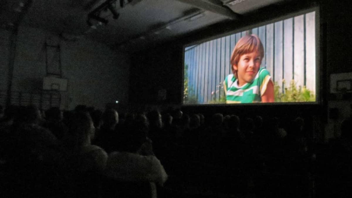 Yleisö katsoo Tumman veden päällä -elokuvaa Maailmanensi-illan yleisö vaikuttui pienen Pete-pojan tarinasta. Peter Franzenin ohjaama Tumman veden päällä esitettiin Keminmaassa lauantaina.