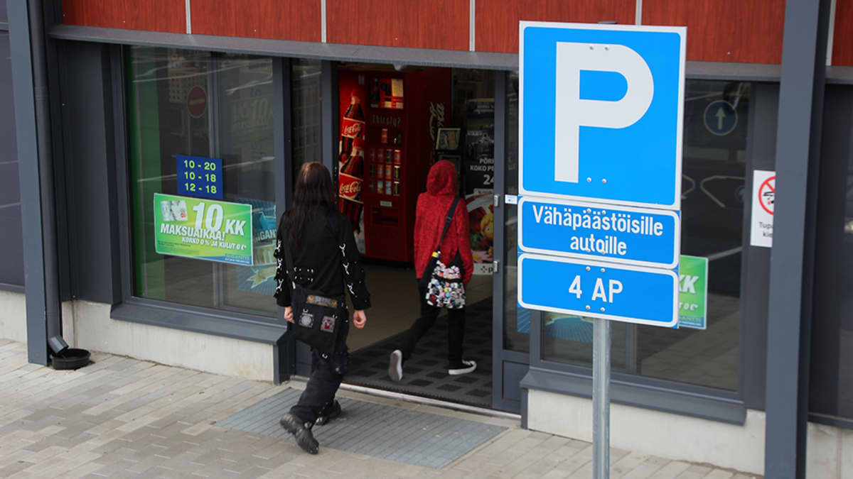 """Pysäköintipaikan merkki, jossa lisäkilpi """"Vähäpäästöisille autoille""""."""